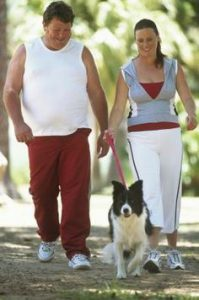 happy couple walking dog